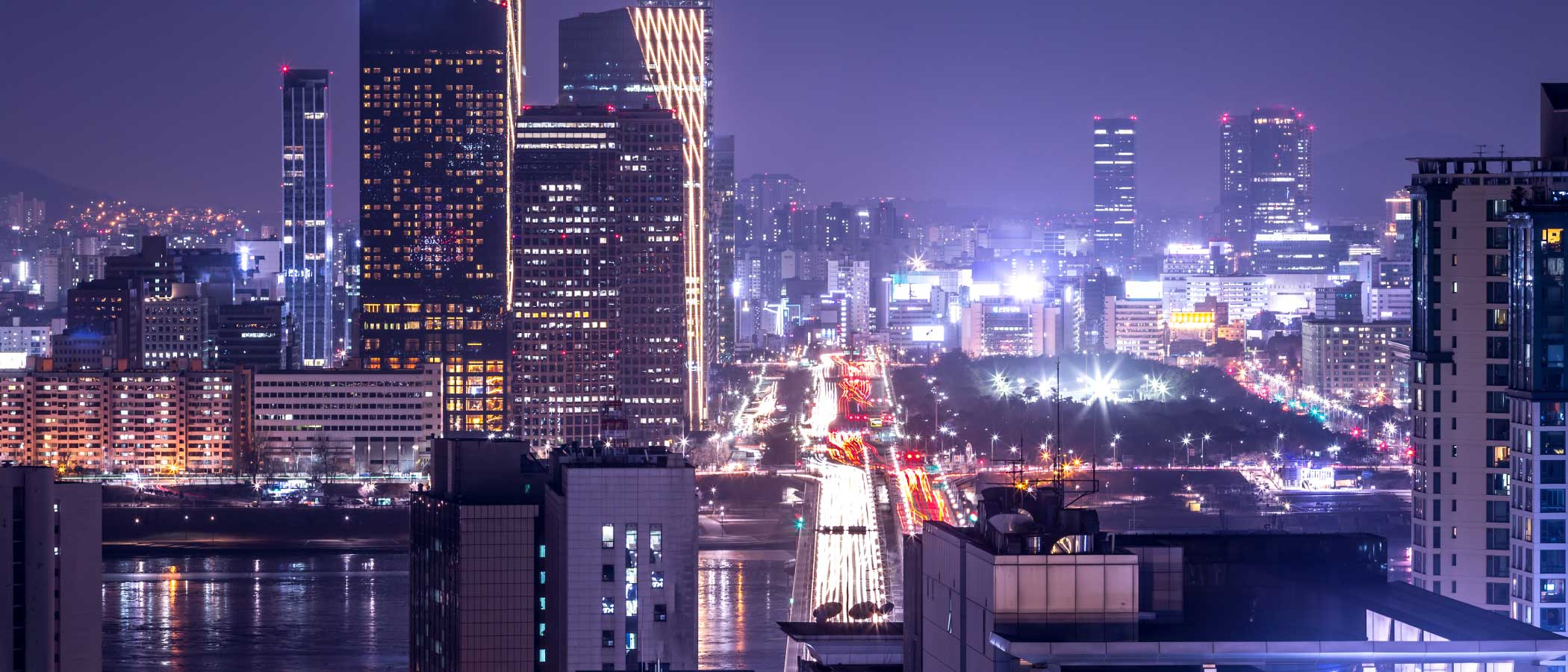 Glowing city skyline with mix of building types from low-rise apartments to high-rise towers.