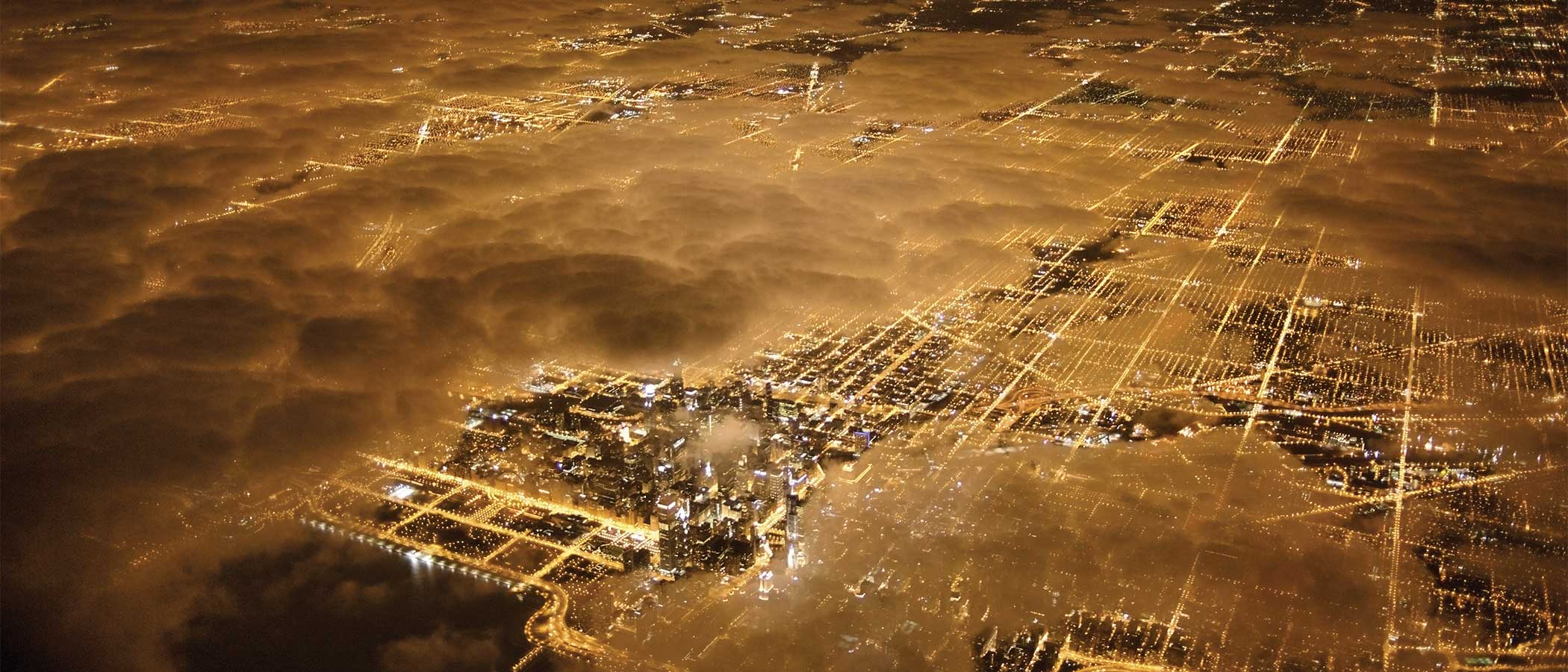 Aerial view of a city at night with glowing lights of buildings and streets