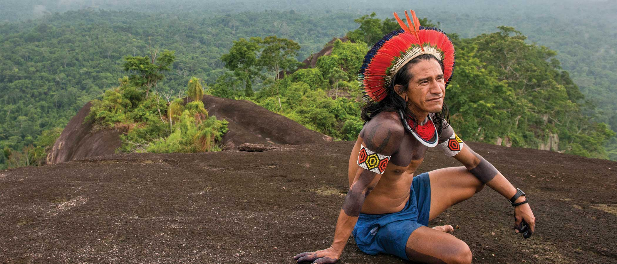 A Kayapo man seated on a mountain top overlooking forest in the Amazon.