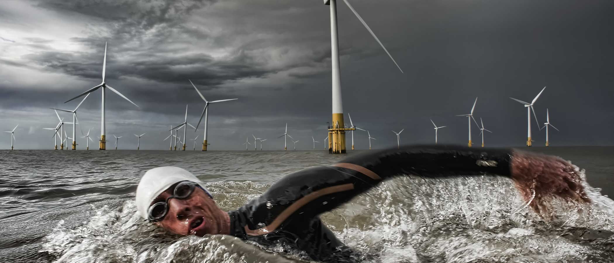 An athlete swims past the Sheringham Shoal Offshore Wind Farm off the coast of Norfolk, England.