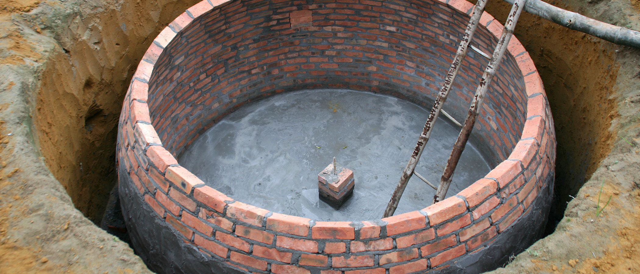 Small-scale biogas plant made of brick and cement then buried below ground.