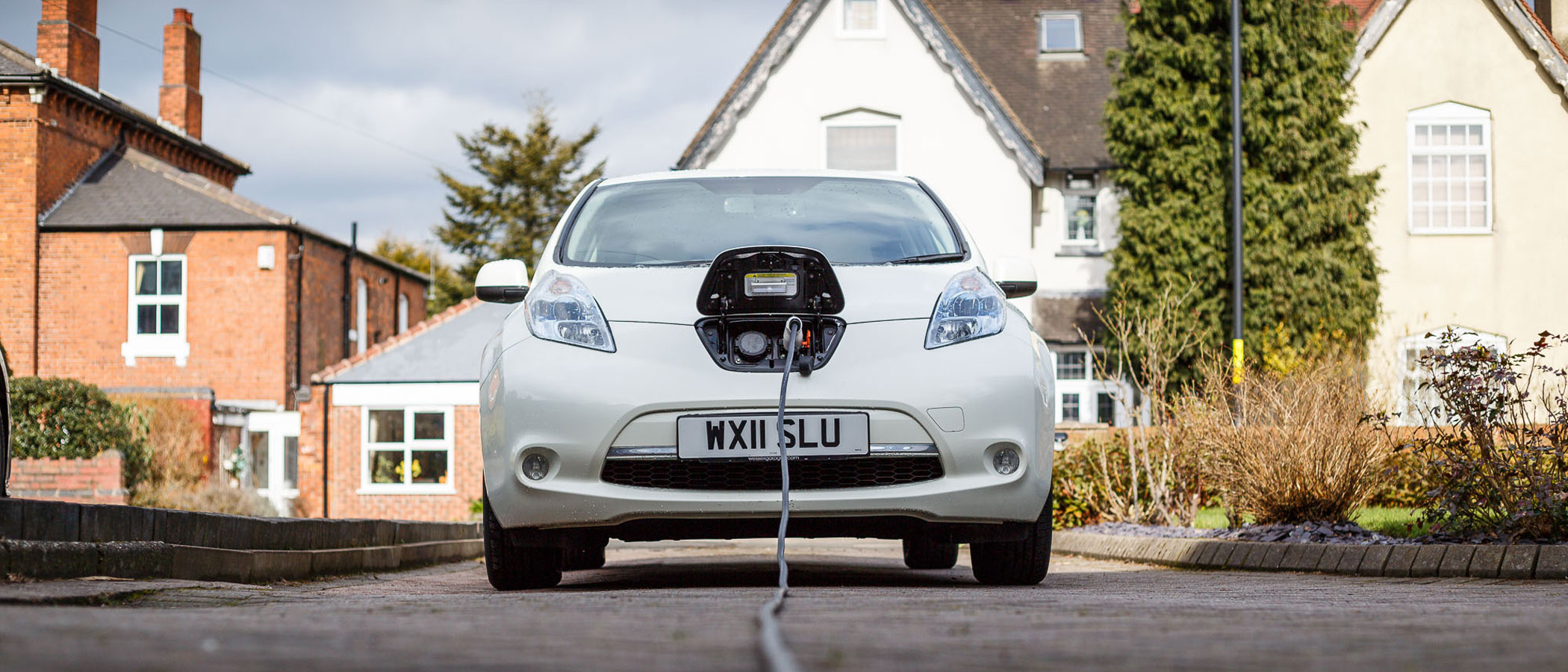 Electric vehicle charging in the driveway of a residence.