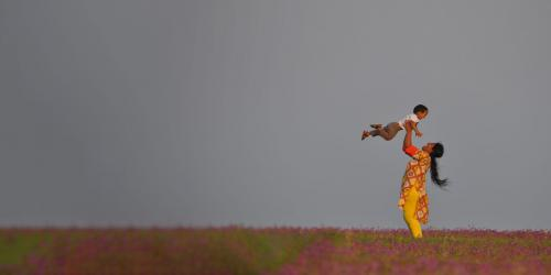 A south asian woman holding a child above her head in a field of wild flowers.