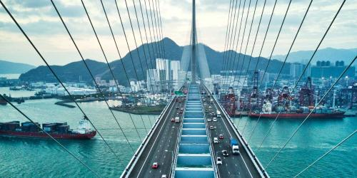 Large suspension bridge highway leading into a city, with a cargo ship passing below.