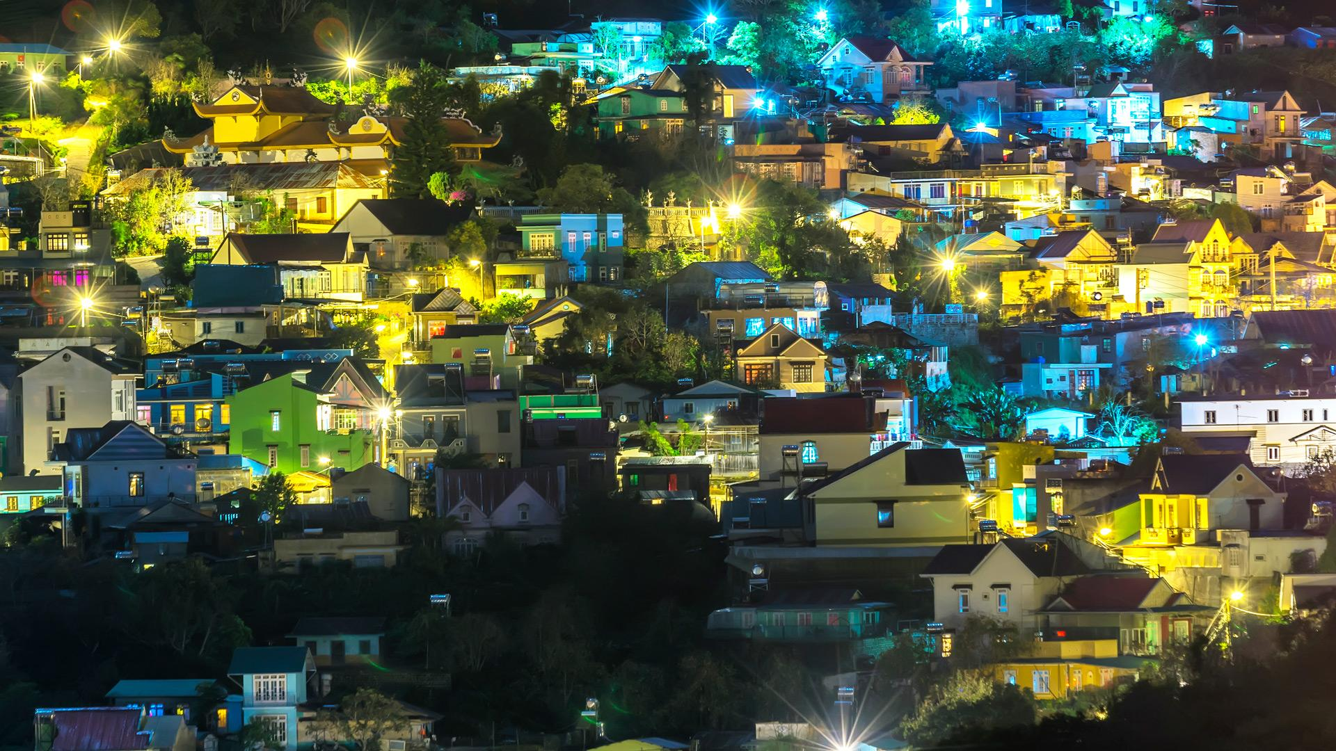 Neighborhood on a hill with lights on at night