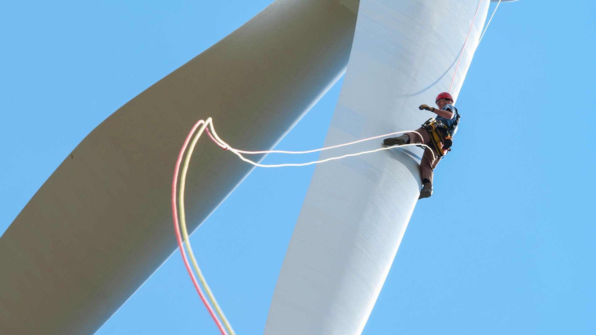 Worker rapelling down a wind turbine blade